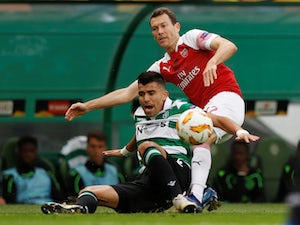 Marcos Acuna and Stephan Lichtsteiner in action during the Europa League group game between Sporting Lisbon and Arsenal on October 25, 2018