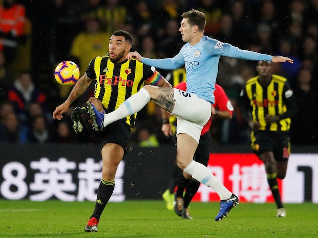 John Stones and Troy Deeney in action during the Premier League game between Manchester City and Watford on December 4, 2018
