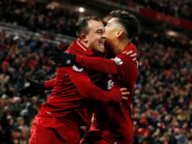 Roberto Firmino embraces Xherdan Shaqiri in celebration during the Premier League game between Liverpool and Manchester United on December 16, 2018