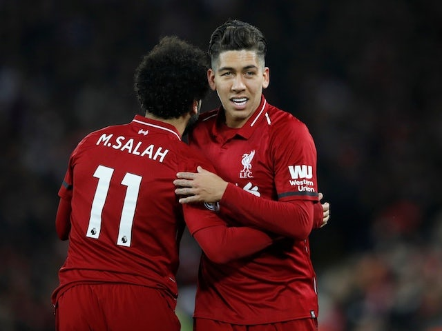 Liverpool striker Roberto Firmino celebrates with Mohamed Salah after scoring against Arsenal on December 29, 2018
