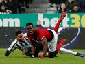 Manchester United's Paul Pogba on the receiving end of a tackle from Newcastle United's Jamaal Lascelles in the Premier League on January 2, 2019.