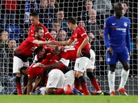 Manchester United's players pile on after Paul Pogba scores their second against Chelsea on February 18, 2019