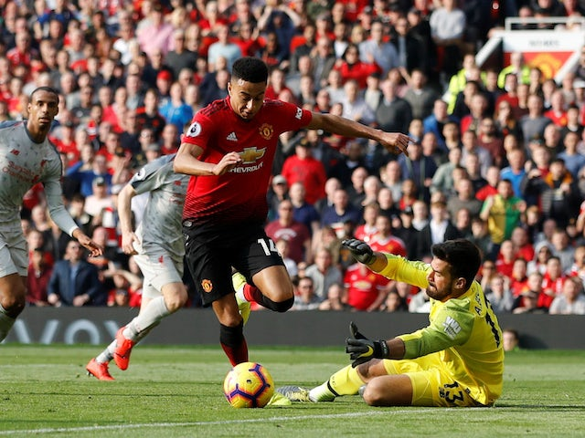 Liverpool goalkeeper Alisson Becker saves from Manchester United's Jesse Lingard in the Premier League on February 24, 2019.