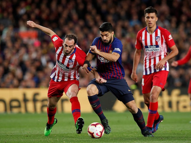 Barcelona's Luis Suarez battles with Atletico Madrid's Diego Godin in their La Liga clash on April 6, 2019