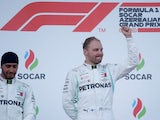 Valtteri Bottas celebrates winning the race on the podium as second placed Lewis Hamilton looks on on April 28, 2019