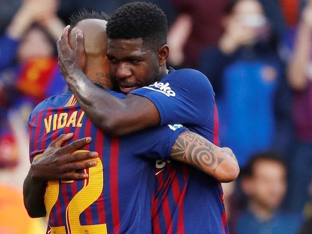 Barcelona's Samuel Umtiti hugs teammate Arturo Vidal during the team's La Liga clash with Getafe on May 12, 2019