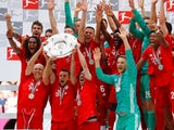 Bayern Munich's Rafinha, Arjen Robben and Franck Ribery lift the trophy as they celebrate winning the Bundesliga title on May 18, 2019