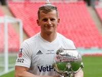 AFC Fylde joker Danny Rowe poses with the FA Trophy partly on his head on May 19, 2019
