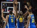 Golden State Warriors forward Draymond Green (23) gives high-fives to teammates center Kevon Looney (5) and forward Alfonzo McKinnie (28) during the second half in game three of the Western conference finals of the 2019 NBA Playoffs at Moda Center on May