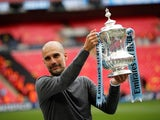 Manchester City manager Pep Guardiola holds the FA Cup aloft on May 18, 2019