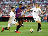 Barcelona's Nelson Semedo battles Valencia's Jose Gaya for the ball during the Copa del Rey final on May 25, 2019