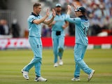 England's Chris Woakes celebrates taking the wicket of New Zealand's Tom Latham with Eoin Morgan on July 14, 2019