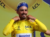 Deceuninck-Quick Step rider Julian Alaphilippe of France celebrates on the podium, wearing the overall leader's yellow jersey on July 8, 2019