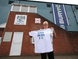 A Bury fan holds up a T-shirt outside Gigg Lane on August 23, 2019