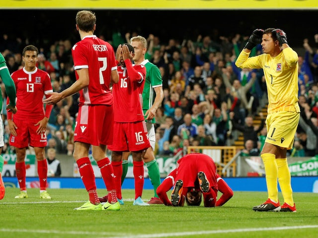 Luxembourg's Kevin Malget is down and dejected after scoring an own goal and Northern Ireland's first as Luxembourg's Anthony Moris reacts on September 5, 2019