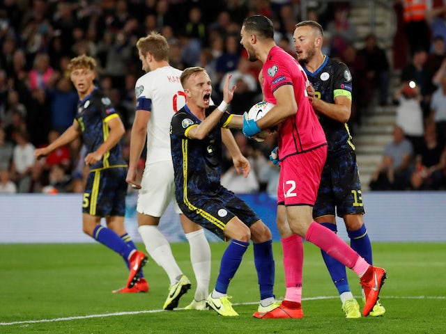 Kosovo's Aro Muric celebrates with Amir Rrahmani after saving a penalty from England's Harry Kane on September 10, 2019