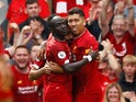 Sadio Mane celebrates his side's second with Roberto Firmino during the Premier League game between Liverpool and Newcastle United on September 14, 2019