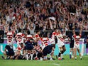 Japan's Isileli Nakajima and team mates celebrate at the end of the match as Scotland players look dejected on October 13, 2019