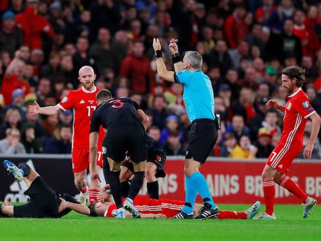 Wales' Daniel James down injured as referee Bjorn Kuipers gestures on October 13, 2019