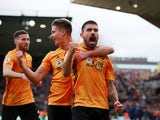 Wolverhampton Wanderers' Ruben Neves celebrates scoring their first goal with Leander Dendoncker and Matt Doherty on November 10, 2019