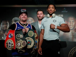 Andy Ruiz Jr and Anthony Joshua pose for a photo in front of promoter Eddie Hearn during the press conference on December 4, 2019