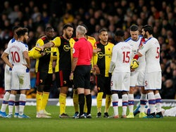 Referee Martin Atkinson speaks with Watford's Troy Deeney as Crystal Palace's Luka Milivojevic reacts after sustaining an injury on December 7, 2019