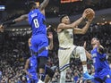 Milwaukee Bucks forward Giannis Antetokounmpo (34) takes a shot between Orlando Magic guard Terrence Ross (8) and forward Aaron Gordon (00) in the second quarter at Fiserv Forum on December 10, 2019