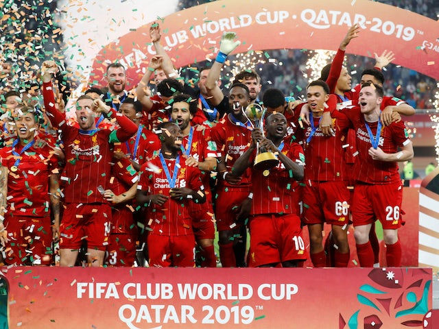Liverpool's Jordan Henderson lifts the trophy as they celebrate after winning the Club World Cup on December 21, 2019