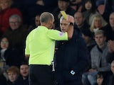 Tottenham Hotspur manager Jose Mourinho is shown a yellow card by referee Mike Dean on January 1, 2020