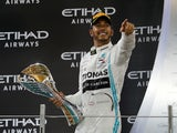 Mercedes' Lewis Hamilton celebrates with a trophy after winning the race on December 1, 2019