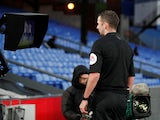 Referee Michael Oliver checks the VAR pitchside monitor before showing a red card to Crystal Palace's Luka Milivojevic on January 5, 2020