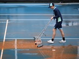 A groundstaff prepares the court ahead of play following a dust storm on January 23, 2020