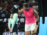 Spain's Rafael Nadal passes the ball girl his head band after winning the match against Argentina's Federico Delbonis on January 23, 2020
