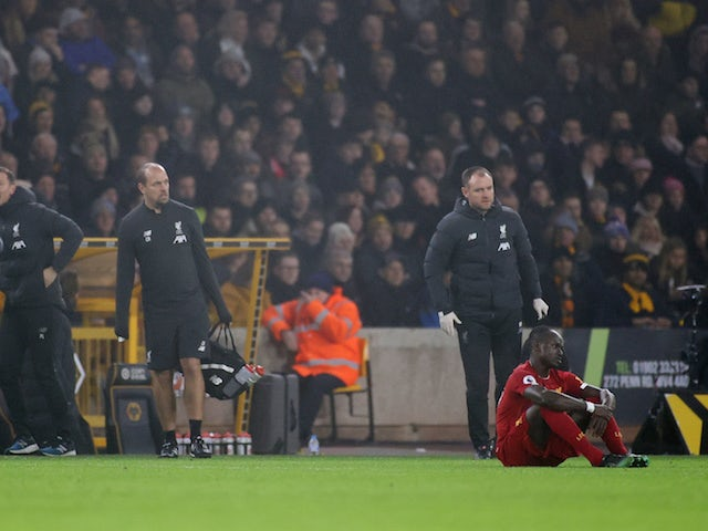 Liverpool's Sadio Mane goes down after sustaining an injury as Liverpool manager Jurgen Klopp reacts on the sideline in January 2020