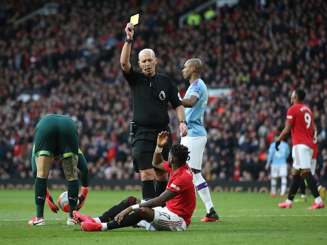 Manchester United's Fred is shown a yellow card by referee Mike Dean on March 8, 2020