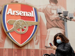 A woman wearing a mask walks by the Emirates Stadium after manager Mikel Arteta tested positive for coronavirus and their Premier League match against Brighton on Saturday has been cancelled on March 13, 2020