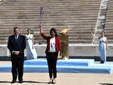 Former Japanese swimmer Imoto Naoko holds the Olympic torch next to Greek Sports Minister and HOC President Spyros Capralos during the olympic flame handover ceremony for the 2020 Tokyo Summer Olympics. The ceremony is being held behind closed doors as th