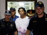 Ronaldinho handcuffed and escorted by police at the Supreme Court of Paraguay in March 2020