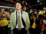 Barcelona coach Johan Cruyff looks on as he is surrounded by photographers after his team defeated Dutch PSV Eindhoven in the second leg of the UEFA Cup quarter final match in Eindhoven, March 19 1996