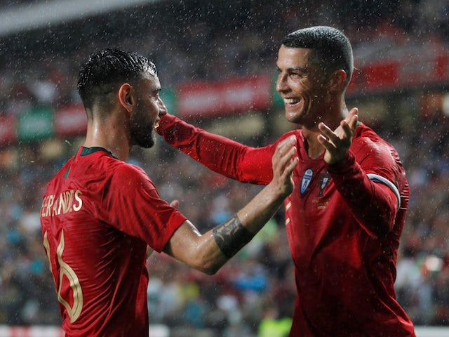 Portugal's Bruno Fernandes celebrates with Cristiano Ronaldo after scoring their second goal in June 2018