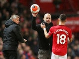 Manchester City manager Pep Guardiola hands the ball to Manchester United's Bruno Fernandes as Manchester United manager Ole Gunnar Solskjaer looks on in March 2020