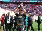 Alex Revell celebrates with the playoff trophy for Rotherham in 2014