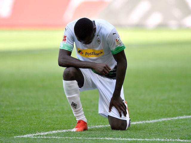 Borussia Monchengladbach's Marcus Thuram takes a knee after scoring on May 31, 2020