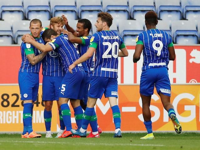 Wigan Athletic players celebrate scoring against Blackburn on June 27, 2020