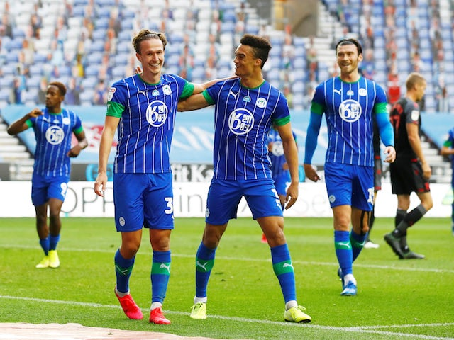 Wigan Athletic players celebrate after a Stoke City own goal on June 30, 2020