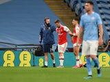 Arsenal defender Shkodran Mustafi is helped off the pitch against Manchester City in their FA Cup semi-final on July 18.