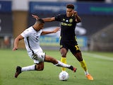 Swansea City's Ben Cabango in action with Brentford's Ollie Watkins in July 2020