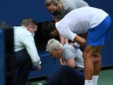 Novak Djokovic attends to a linesperson who was struck by a ball at the US Open on September 6, 2020
