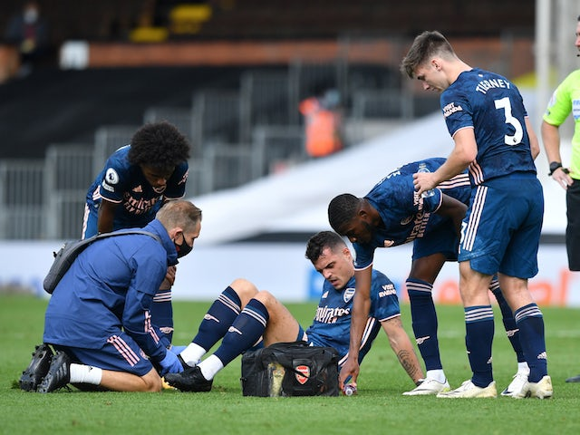 Arsenal's Granit Xhaka receives treatment for an ankle injury against Fulham on September 11, 2020