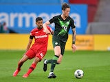Bayer Leverkusen's Kerem Demirbay in action with Wolfsburg's Wout Weghorst in the Bundesliga in May 2020